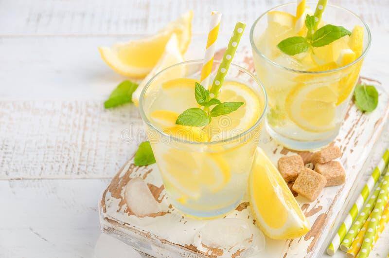 Koude verfrissende de zomerdrank met citroen en munt op houten achtergrond stock afbeeldingen