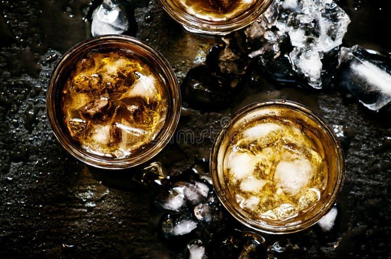 Koude whisky in een glas met verpletterd ijs op een zwarte steen natte bedelaars stock foto