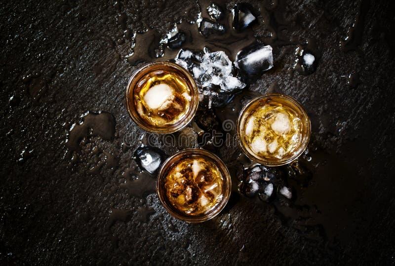 Koude whisky in een glas met verpletterd ijs op een zwarte steen natte bedelaars stock fotografie