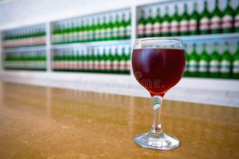 Koude wijn in een glas op de achtergrond van flessen royalty-vrije stock foto's