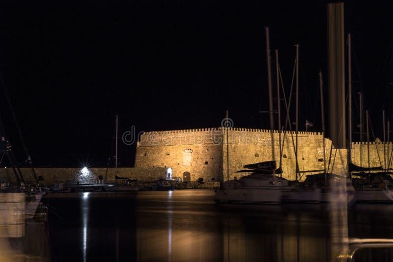 Koules venetian fästning av långa exponeringsfartyg för natt som svävar lugna nattsommar heraklion royaltyfri foto