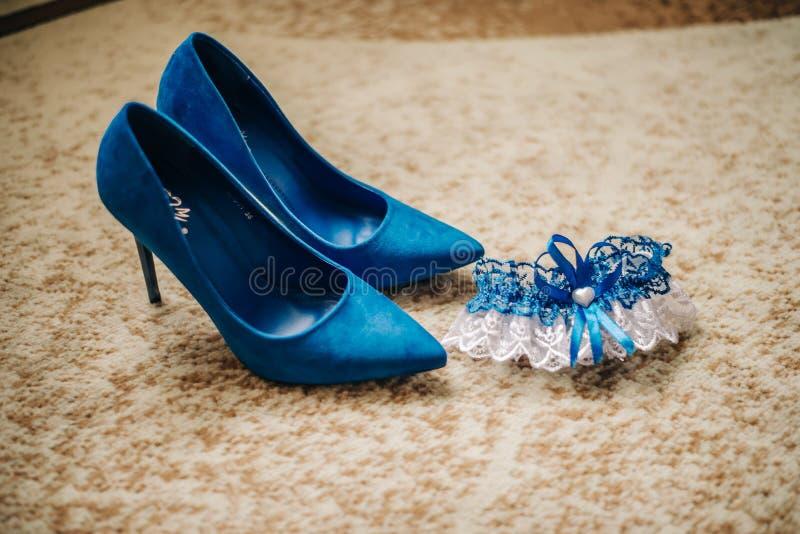 Kouseband van een bruid en high-heeled schoenen stock afbeeldingen