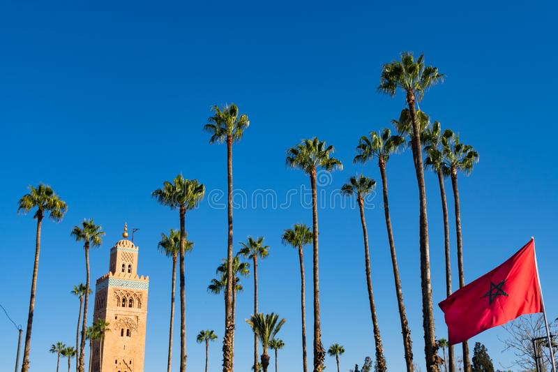 Koutoubia drzewka palmowe z marokańczyk flagą w Marrakesh Maroko i meczet obrazy stock