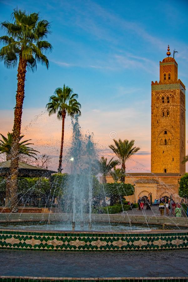 Koutoubia Mosque with fountain in the foreground. Palm trees, fountain and mosque in the twilight in Marrakech. A blue sky background creates an atmospheric royalty free stock image