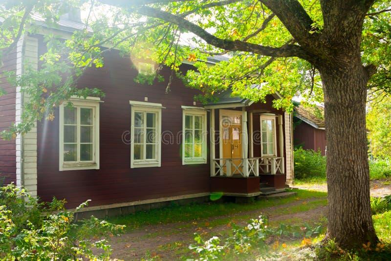 KOUVOLA, ФИНЛЯНДИЯ - 20-ОЕ СЕНТЯБРЯ 2018: Красивый красный старый деревянный дом и большое дерево на территории поместья Anjala стоковое фото rf