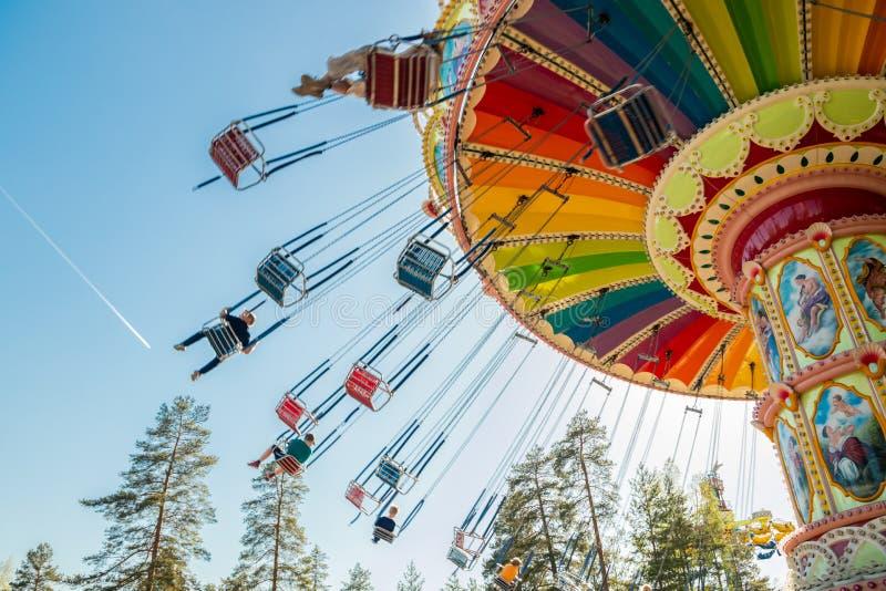 Kouvola, Финляндия - 18-ое мая 2019: Carousel качания езды в движении в парке атракционов Tykkimaki и след воздушных судн в небе стоковые изображения