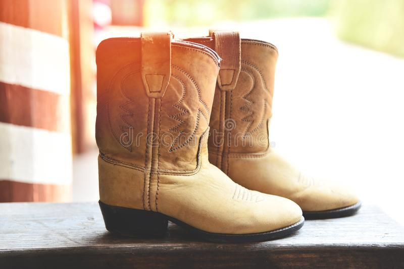 Kowbojscy buty - Amerykańska Dzika Zachodnia retro kowbojska rodeo para tradycyjny rzemienny Roper stylu western na drewnianym ro obraz royalty free
