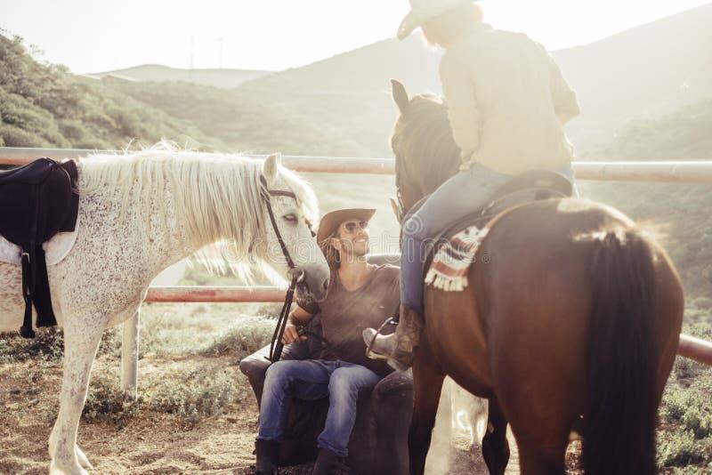 Kowbojska scena dla plenerowej czas wolny aktywności dla mężczyzny, kobieta i dwa konie zdjęcie royalty free