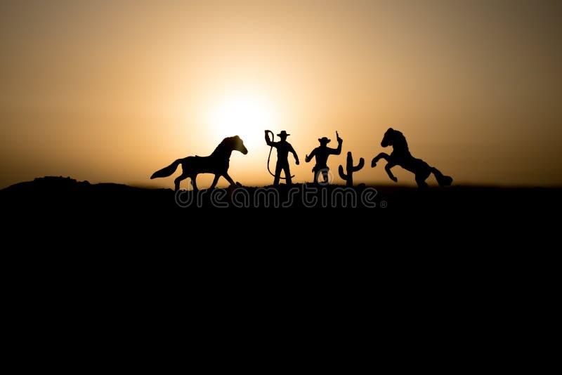 Kowbojski pojęcie Sylwetka kowboje przy zmierzchu czasem Kowboj sylwetki na wzgórzu z koniami zdjęcie stock