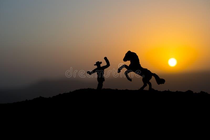 Kowbojski pojęcie Sylwetka kowboje przy zmierzchu czasem Kowbojska sylwetka na górze z żółtym niebem fotografia stock