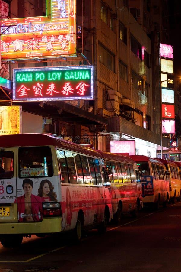 Kowloon, Hong Kong: Autobuses de la ciudad en la noche bajo señales de neón fotografía de archivo