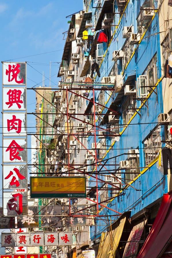 Vista a la fachada vieja del rascacielos con las cajas y la publicidad de la condición del aire imagenes de archivo