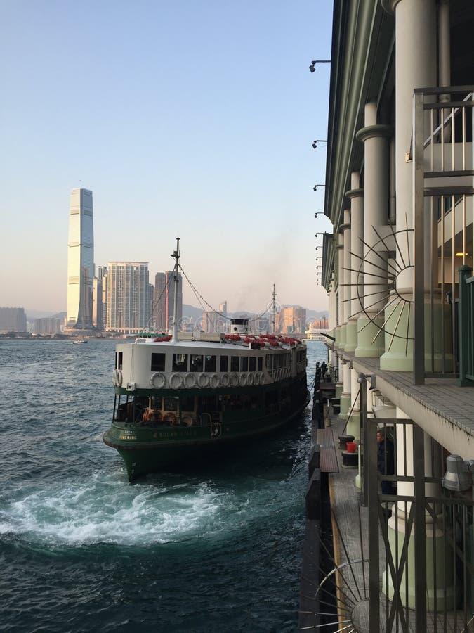 Kowloon, Hong Kong: Transbordador de la estrella que sale del muelle en la puesta del sol fotografía de archivo