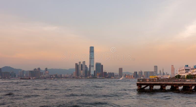 Kowloon korsar Victoria Harbor på solnedgången som beskådas från Sai Wan eller västra ögla av Hong Kong Island arkivfoto