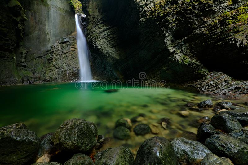 Kozjak Waterfalls, Kobarid, Julian Alps, Slovenia in Europe. Green lake surface in rock gorge, big wet stones in the foreground. W. Ater in the big waterfall royalty free stock images
