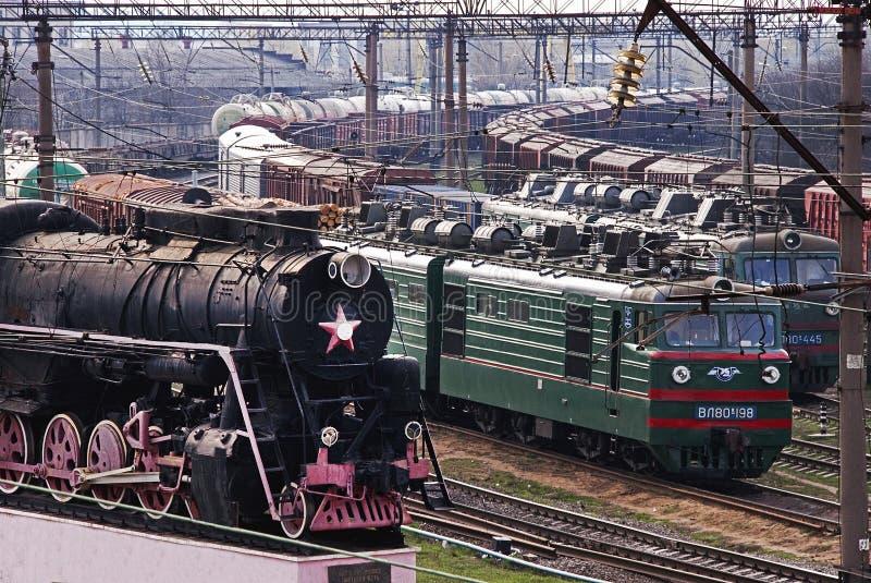 Kozyatyn, de Oekraïne - April 10, 2010: Oude historische stoomtrein en nieuwe goederentreinen stock afbeeldingen