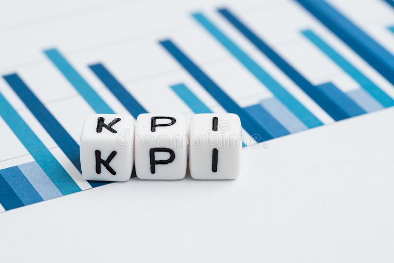 KPI, concepto de indicador de rendimiento clave, bloque de cubo pequeño con alfabetos que crean la palabra KPI en informes de grà fotos de archivo