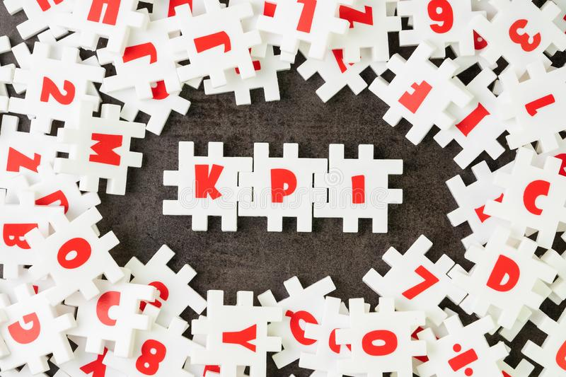 KPI, Key Point Indicator concept, white puzzle jigsaw alphabet combine word KPI at the center on dark black cement floor, business stock photos