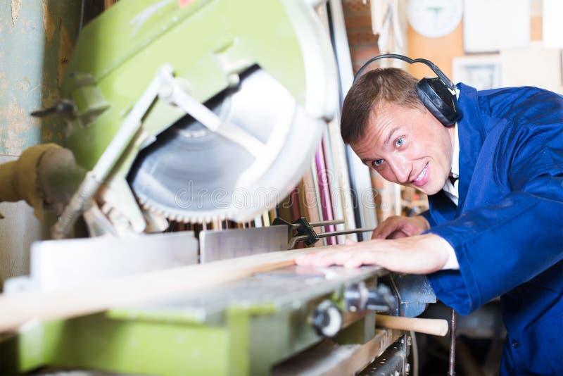 Kräftiger Arbeiter, der hölzerne Planken unter Verwendung der Kreissäge schneidet stockfoto