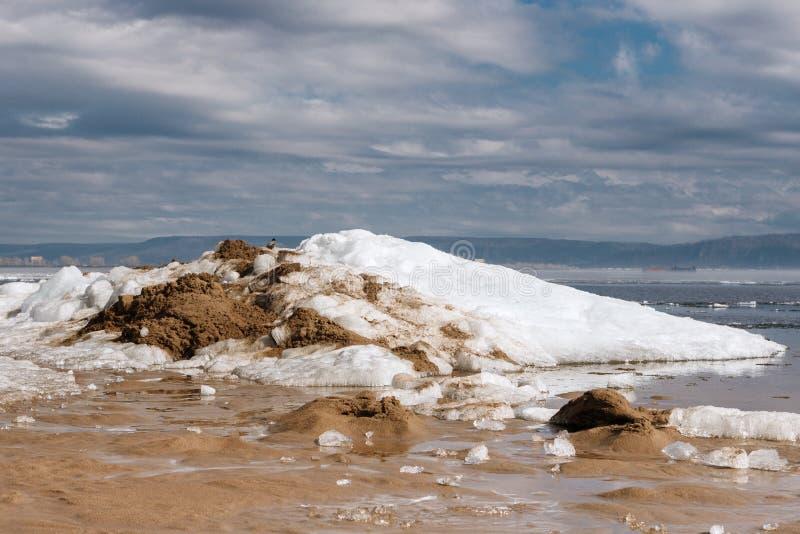 Krähe, die auf einem sandig-schneebedeckten Berg sitzt stockfoto