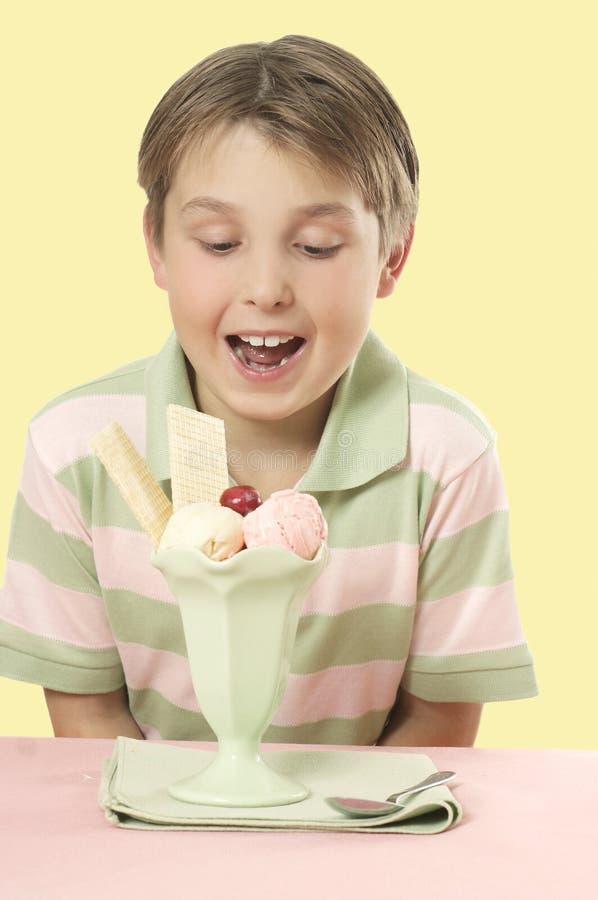 kräm- is för barn som ser sundaetabellen arkivfoton