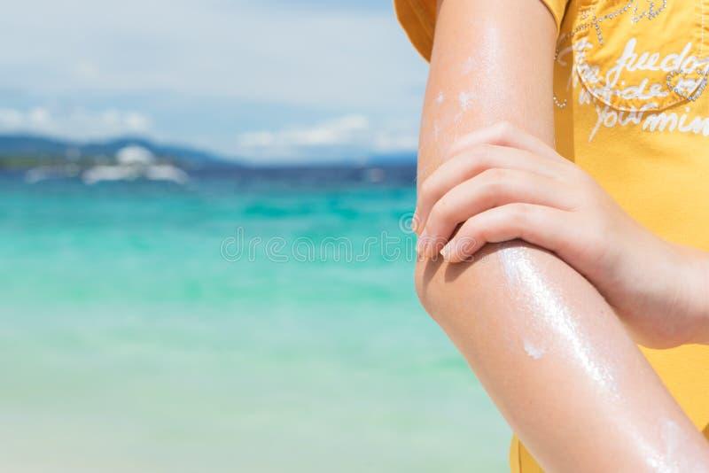 Kräm för beskyddande för ung flickaapplyngsol på hennes hand på det tropiska turkoshavet för strand nästan under blå himmel arkivbild