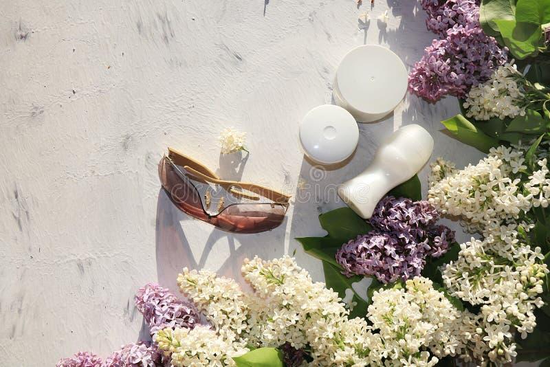 Kräm för kroppomsorg och deodorant på en solig tabell med filialer av lilan som förbereder sig för sommar att vila i solen, kopie arkivfoto