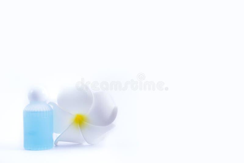Kräm- flaska och plumeriablomma royaltyfri fotografi