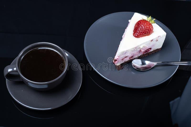 Kräm- fruktkaka och en kopp av svart kaffe på en svart exponeringsglastabell arkivbild