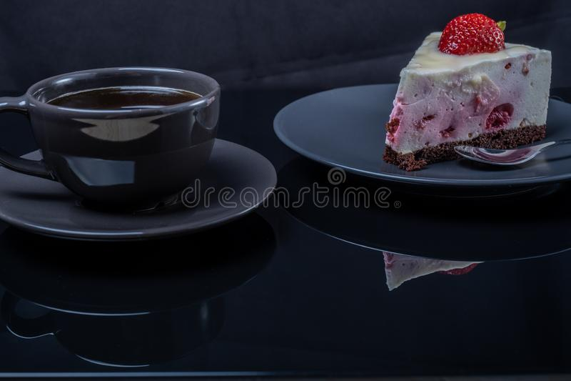 Kräm- fruktkaka och en kopp av svart kaffe på en svart exponeringsglastabell arkivfoton