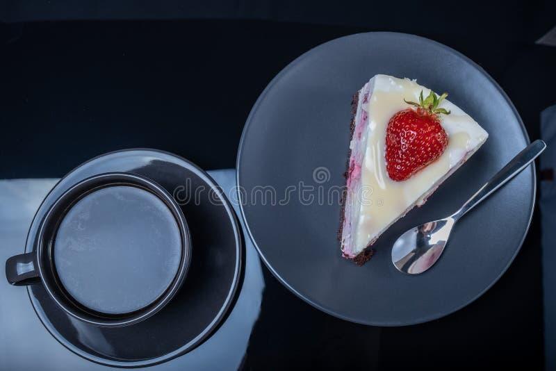 Kräm- fruktkaka och en kopp av svart kaffe på en svart exponeringsglastabell royaltyfria foton
