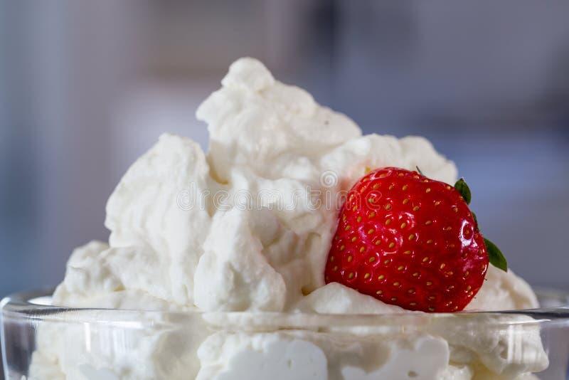 Kräm med jordgubbar i en glass bunke arkivfoto