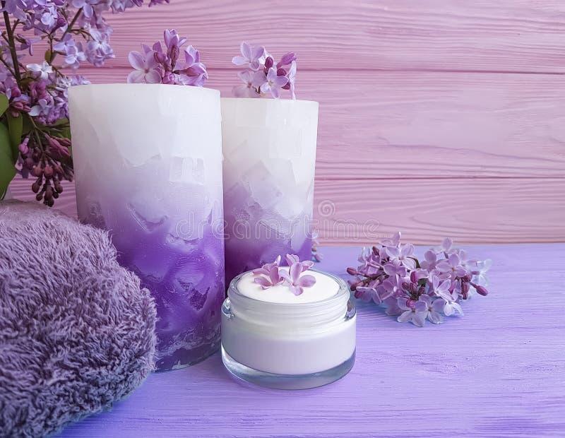 Kräm- naturlig kosmetisk lila på trä, handduk, stearinljus royaltyfria foton