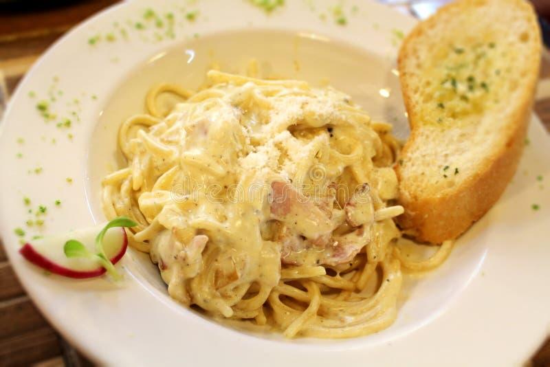 """Kräm- sås för klassisk för stilpasta""""carbonara†spagetti för  med grisköttkinder, parmesanost och sidomaträtten arkivfoto"""