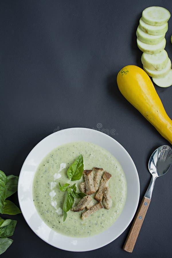 Kräm- soppa av mosade potatisar med zucchinin och basilika och smällare på en mörk bakgrund Utrymme f?r text arkivfoton