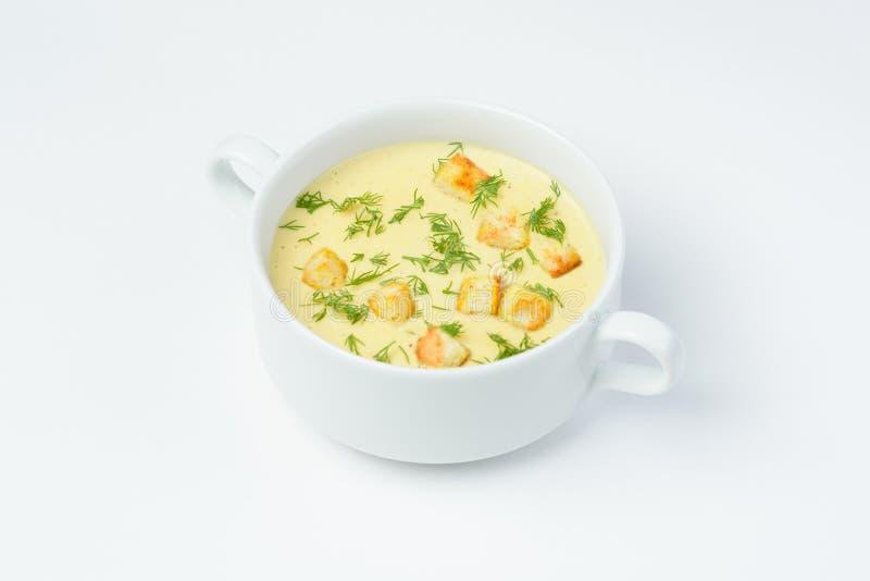 Kräm- soppa för ost med krutonger och nya örter på en vit bakgrund royaltyfria foton