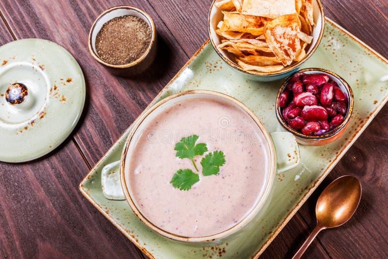 Kräm- soppa med bönor, grönsaker, örter och smällare på plattan på mörk träbakgrund var kunde den hemlagade pien för mat arkivfoto