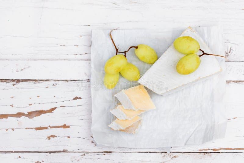 Krämig Brie på vit lantlig träbakgrund, bästa sikt royaltyfri bild
