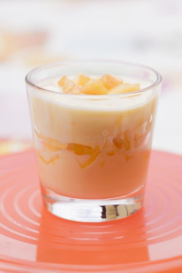 Krämig gul fruktefterrätt i klart exponeringsglas arkivfoton