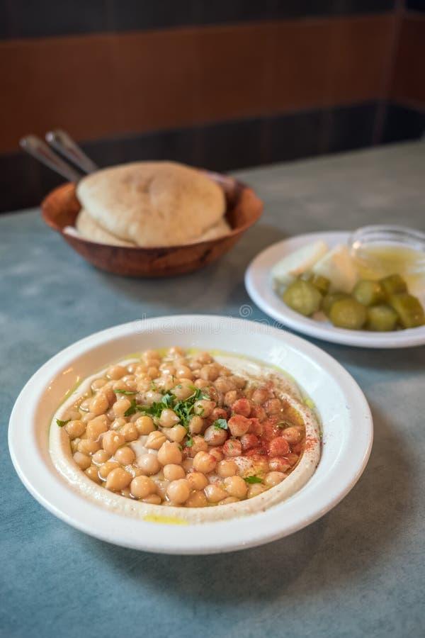 Krämig hummus med hela cheakpeas tätt upp, hög av pitabröd och knipor på bakgrunden royaltyfri foto
