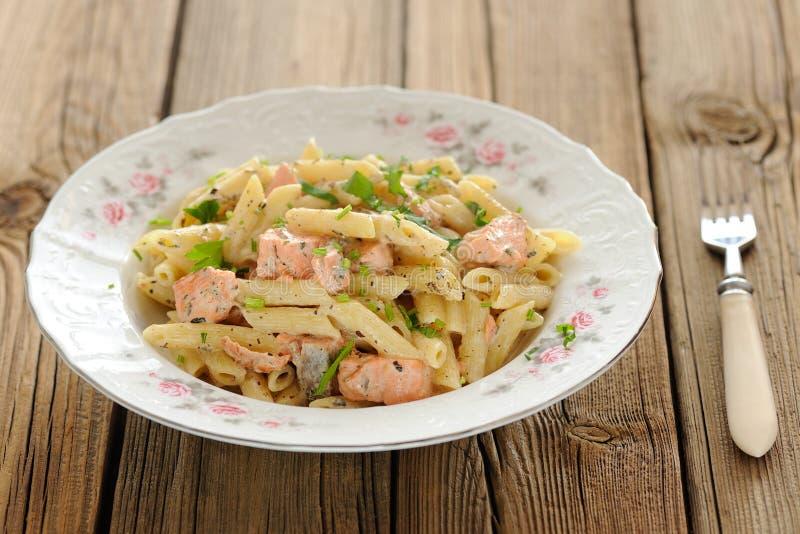 Krämig pasta med laxen och persilja i den vita plattan arkivbild