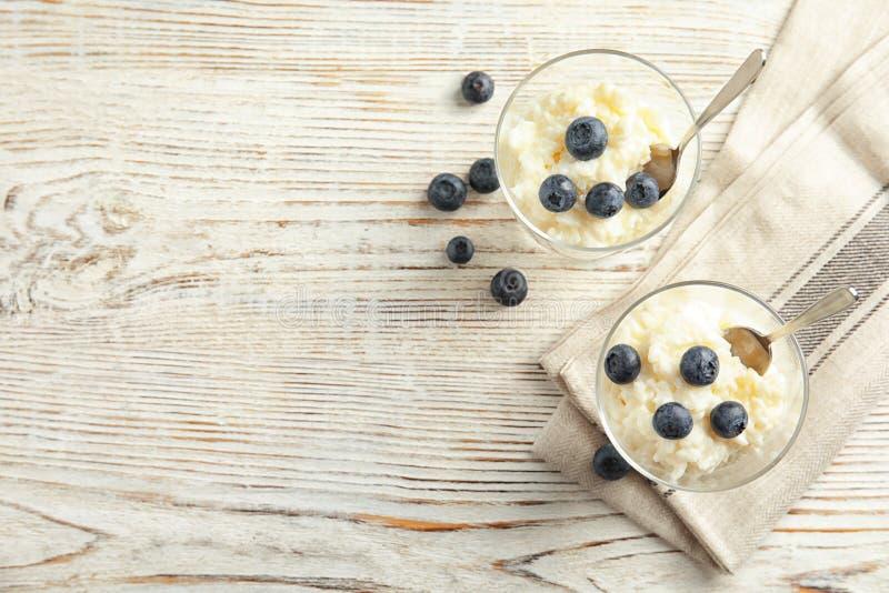 Krämig risgrynsgröt med blåbär i efterrättbunkar på den vita trätabellen, bästa sikt arkivbild