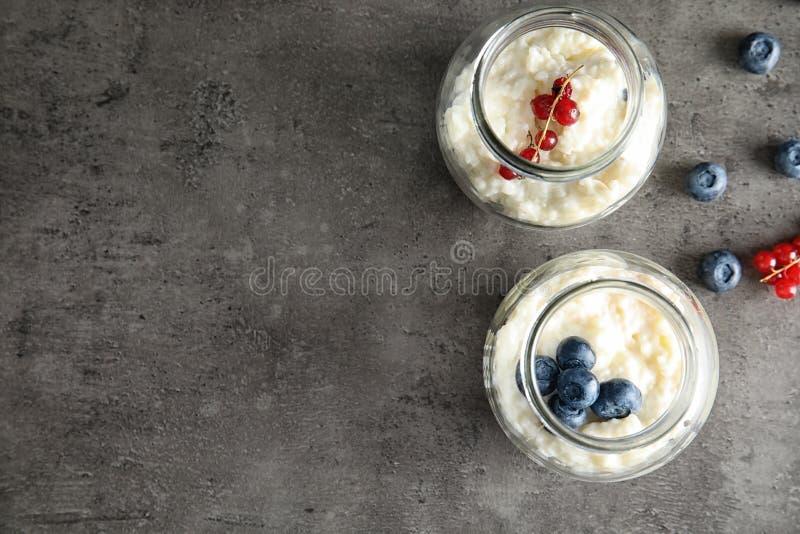 Krämig risgrynsgröt med den röda vinbäret och blåbär i krus på grå bakgrund, bästa sikt royaltyfri bild