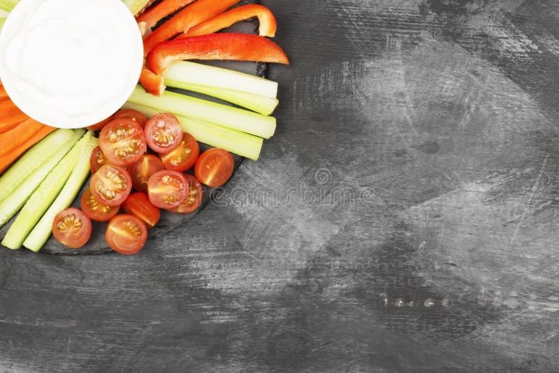 Krämig sås i den vita bunken och olika grönsaker royaltyfria bilder