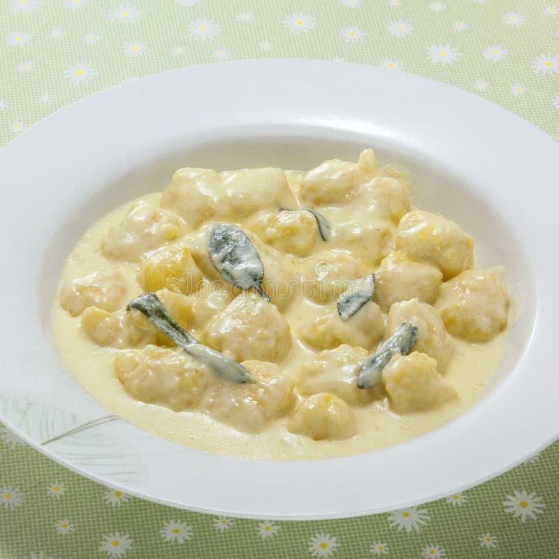 Krämig sötpotatissoppa med currybladet på det vita uppläggningsfatet arkivbild