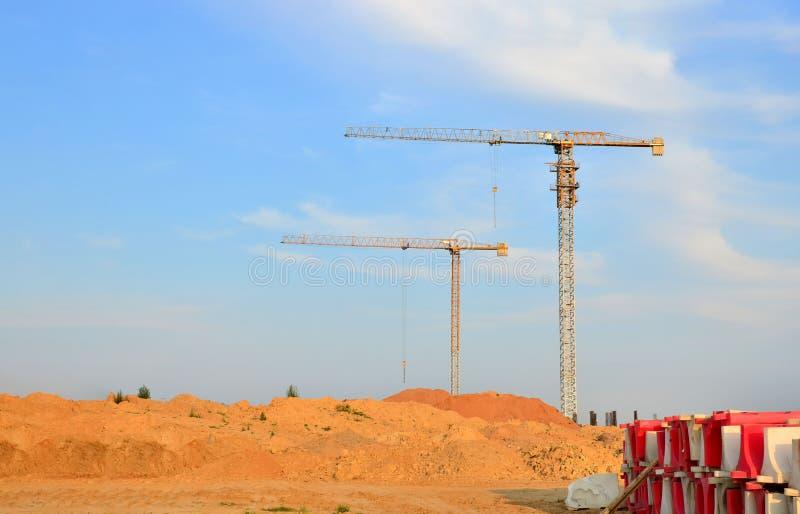 Kräne aus Jib-Bauturm an einer Baustelle auf blauem Himmelshintergrund stockfotografie