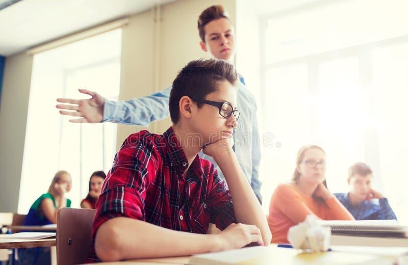 Kränkande studentpojke för klasskompis på skolan fotografering för bildbyråer