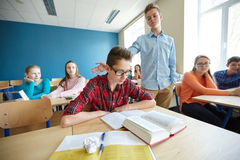 Kränkande studentpojke för klasskompis på skolan arkivfoton