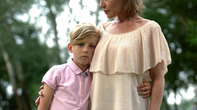 Kränkt pojke som omfamnar modern, problem på skola, brist av vänner och dåliga fläckar royaltyfria foton