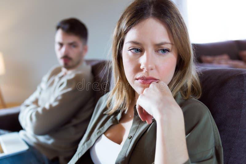 Kränkt ung kvinna som hemma ignorerar hennes ilskna partnersammanträde bak henne på soffan arkivbild